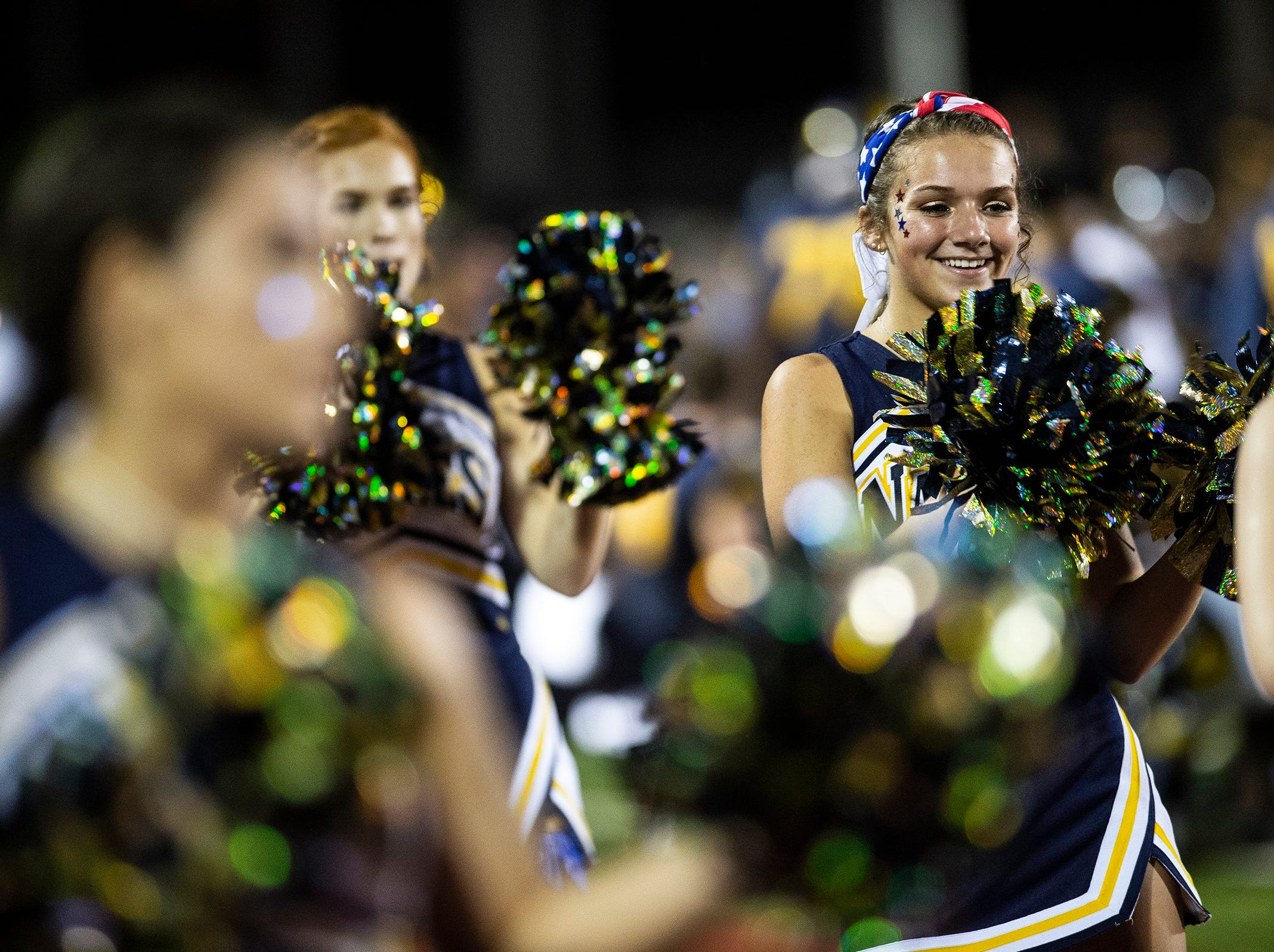 Naples High School' cheerleaders pump up the crowd during a game against Immokalee High School in Naples, Fla. on Friday, September 21, 2018.
