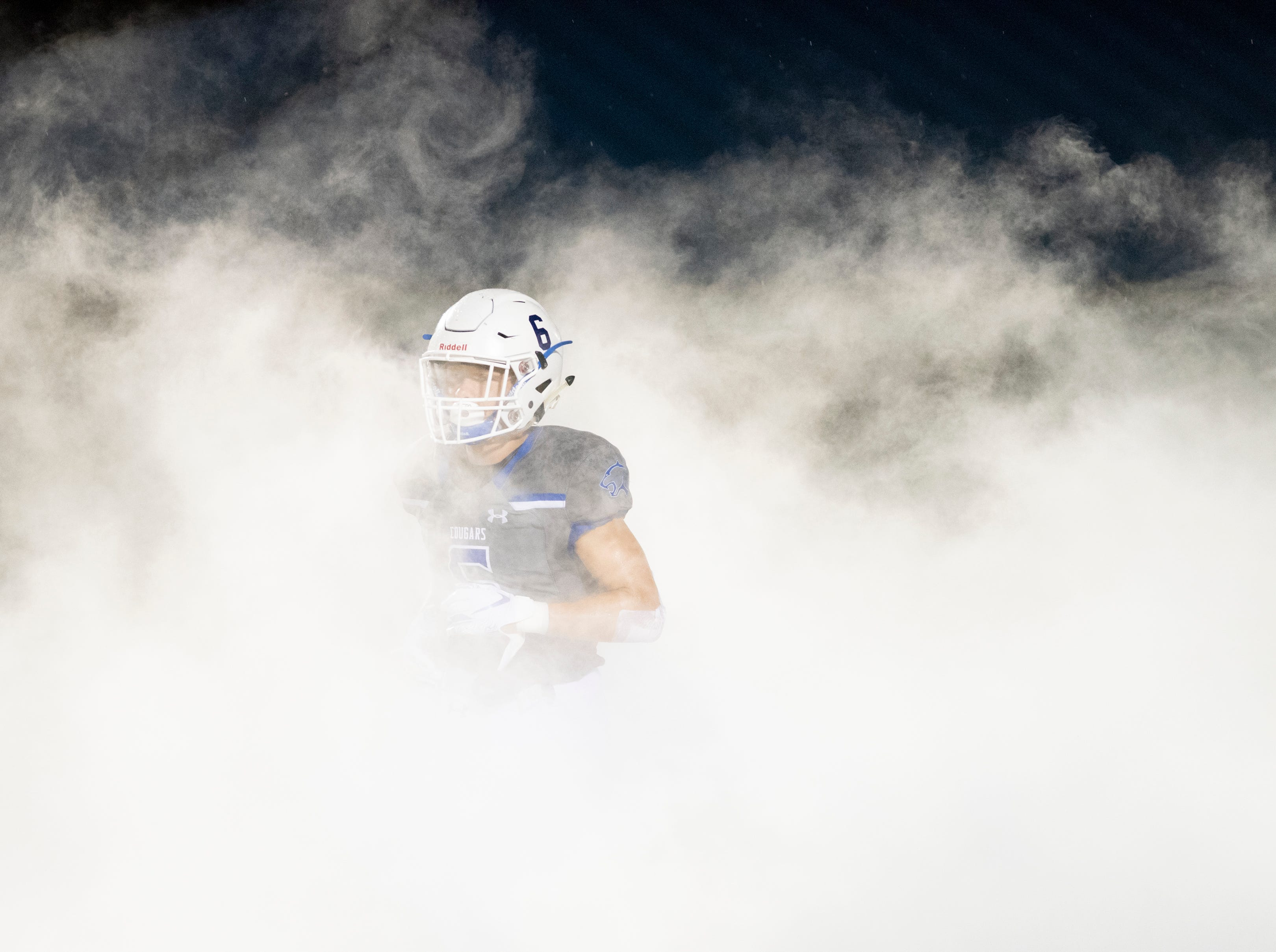 Christopher Crouch of Barron Collier enters through the smoke before the start of the game against Mariner at Barron Collier High Friday night, September 21, 2018.