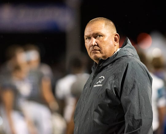 Barron Collier head coach Mark Jackson watches his team warm up in the rain before the start of the game against Mariner at Barron Collier High Friday night, September 21, 2018.