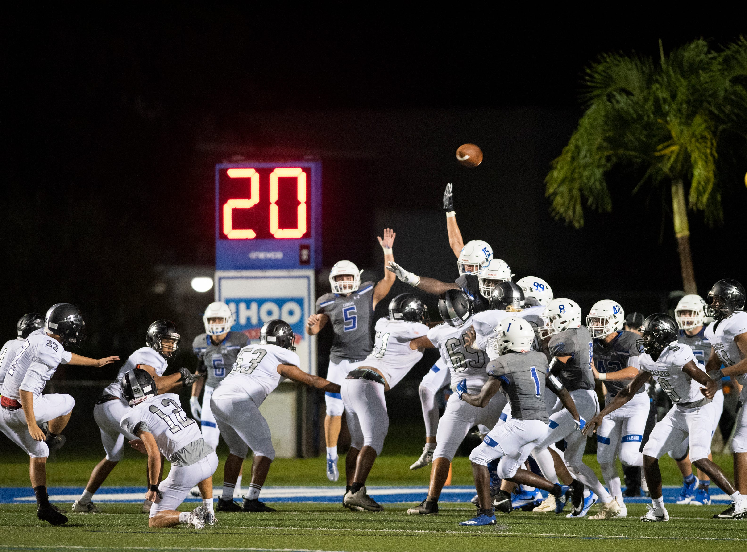 Kaleb Manley of Mariner kicks an extra point as Barron Collier tries to block it during the game at Barron Collier High Friday night, September 21, 2018.