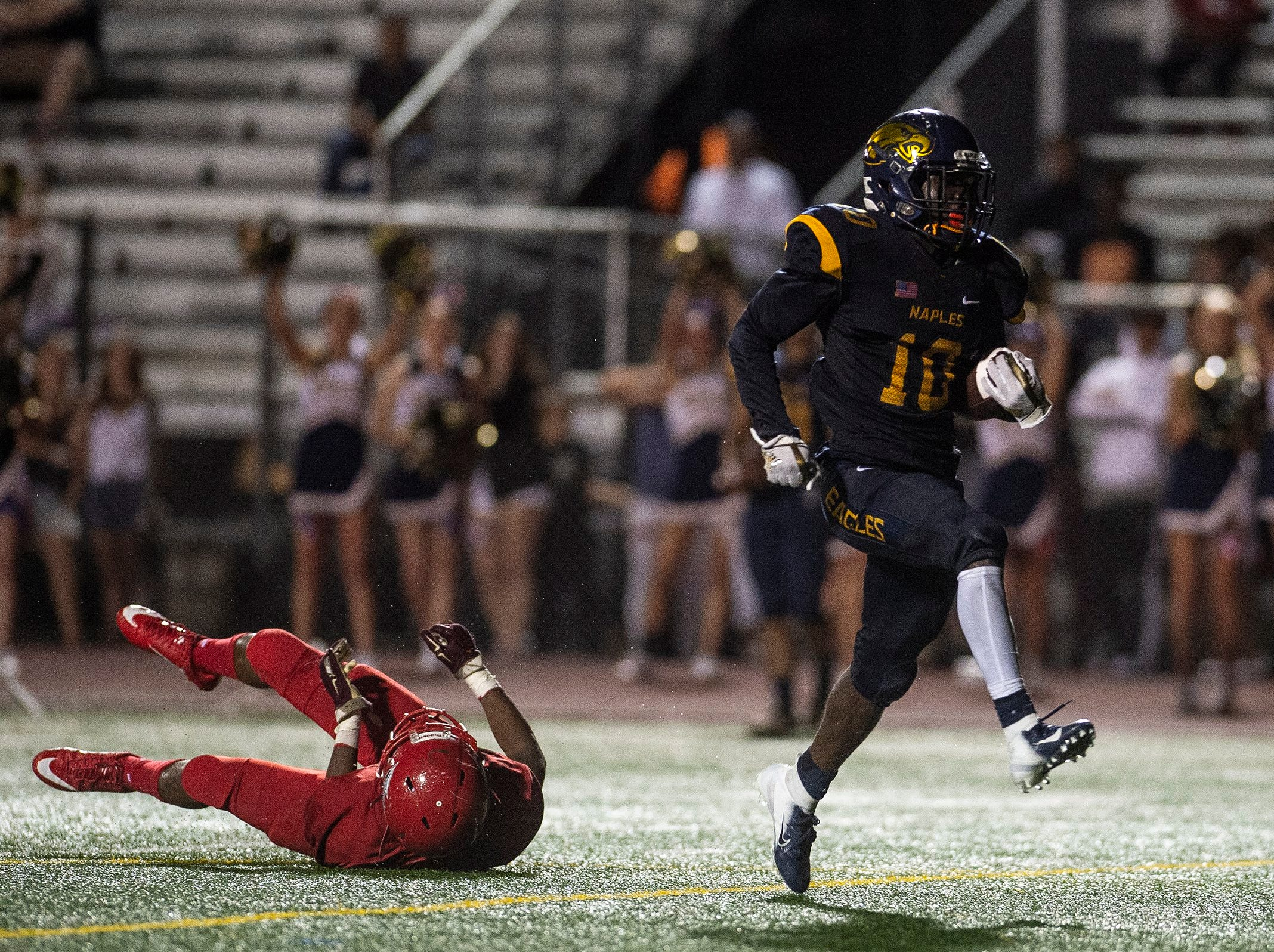 Naples High School's D'Andre St Jean shakes off a tackle that results in a touchdown run during a game against Immokalee High School in Naples, Fla. on Friday, September 21, 2018.