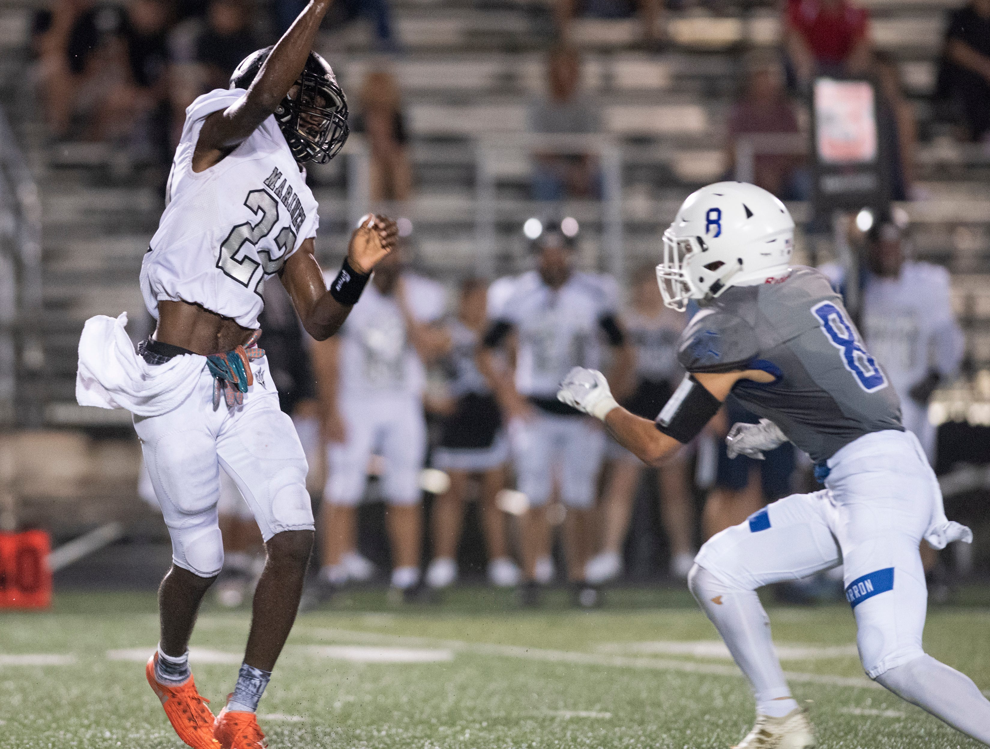 Mariner quarterback Rashawn Hunter throws a pass over Tyler Echeverry of Barron Collier during the game at Barron Collier High Friday night, September 21, 2018.