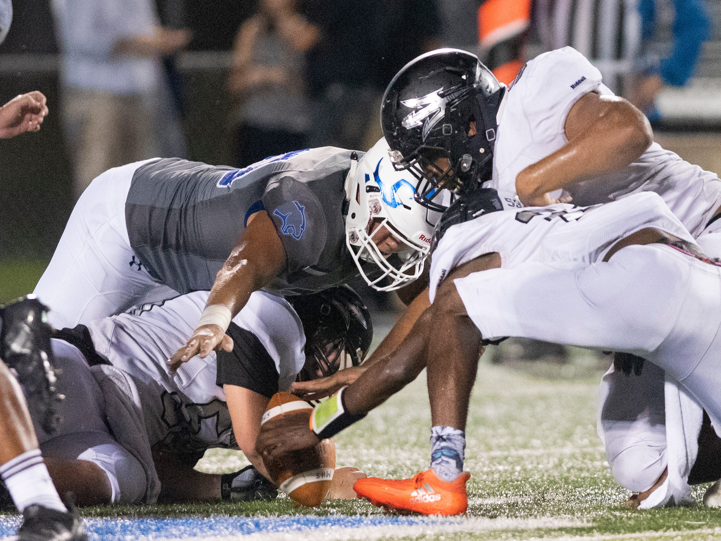 The Barron Collier defense and the Mariner offense dive for a Mariner fumble during the game at Barron Collier High Friday night, September 21, 2018.