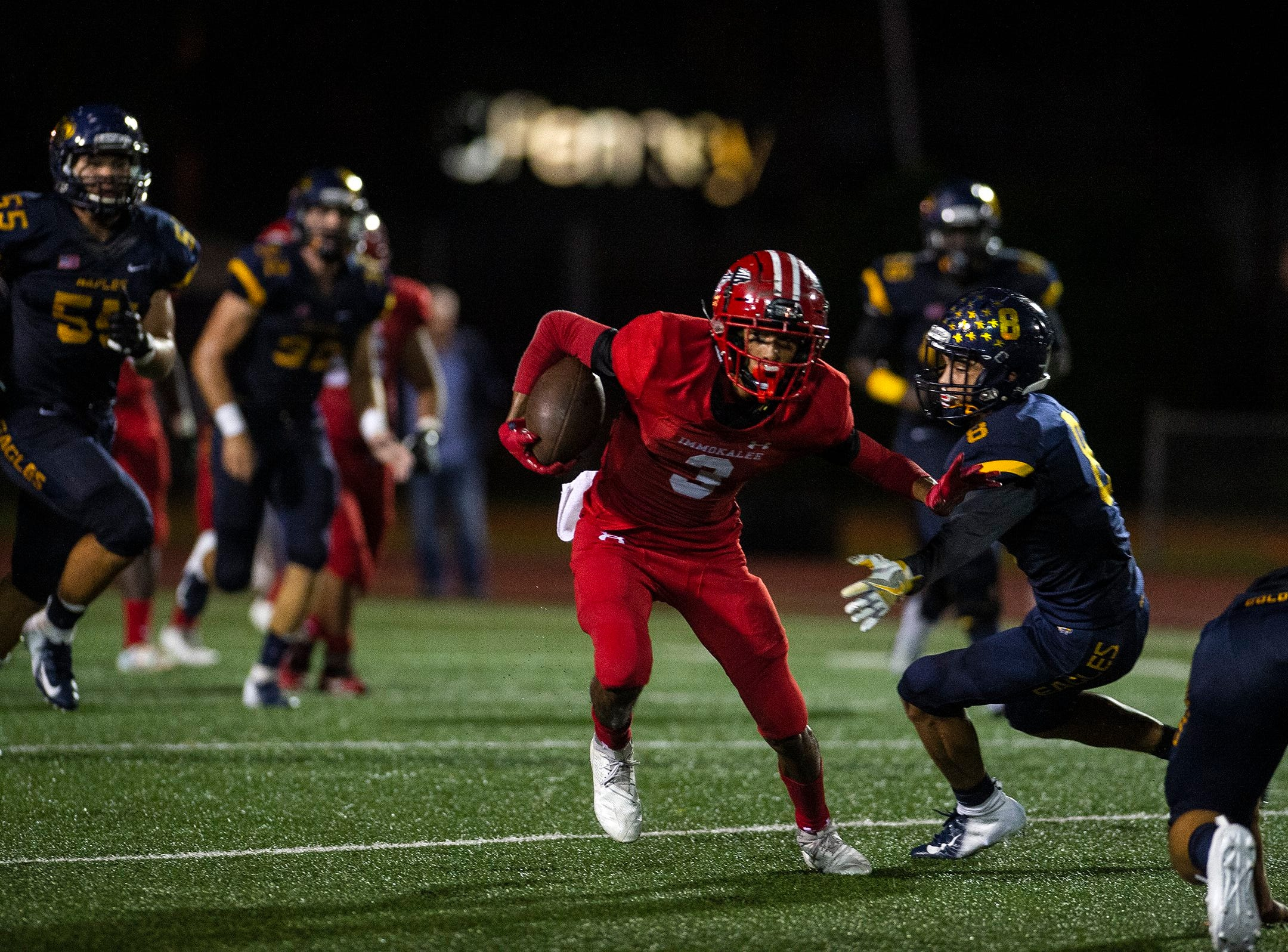 Immokalee High School's Jodeci Chappa pushes off Naples High School's Tre Smith(8) during a game against Naples High School in Naples, Fla. on Friday, September 21, 2018.