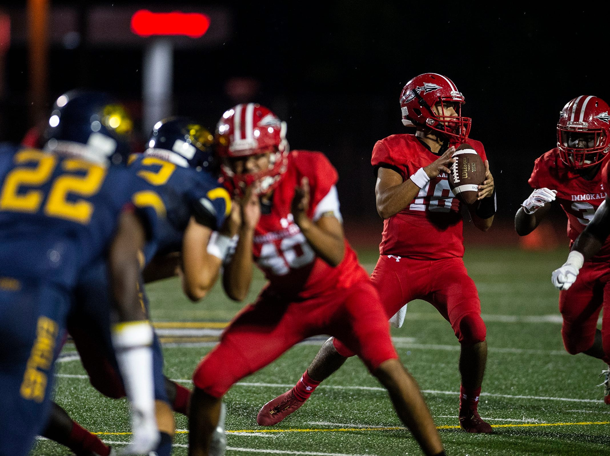 Immokalee High School quarterback Reynaldo Rosales looks for an open pass during a game against Naples High School in Naples, Fla. on Friday, September 21, 2018.