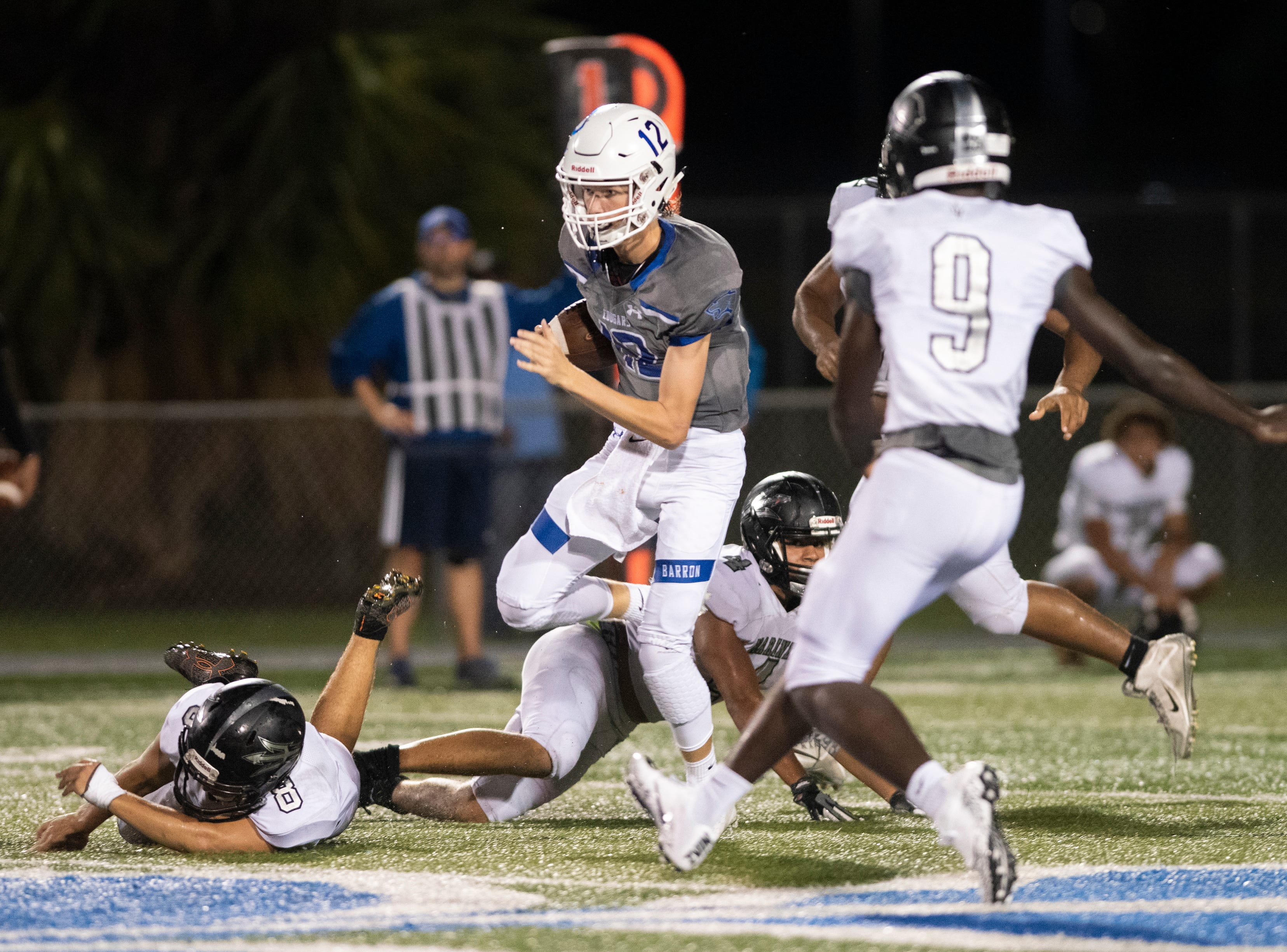Barron Collier quarterback Jason Grimes runs through the Mariner defense during the game at Barron Collier High Friday night, September 21, 2018.