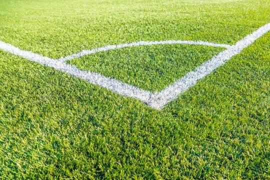 Corner kick football/soccer field outline on green artificial grass.