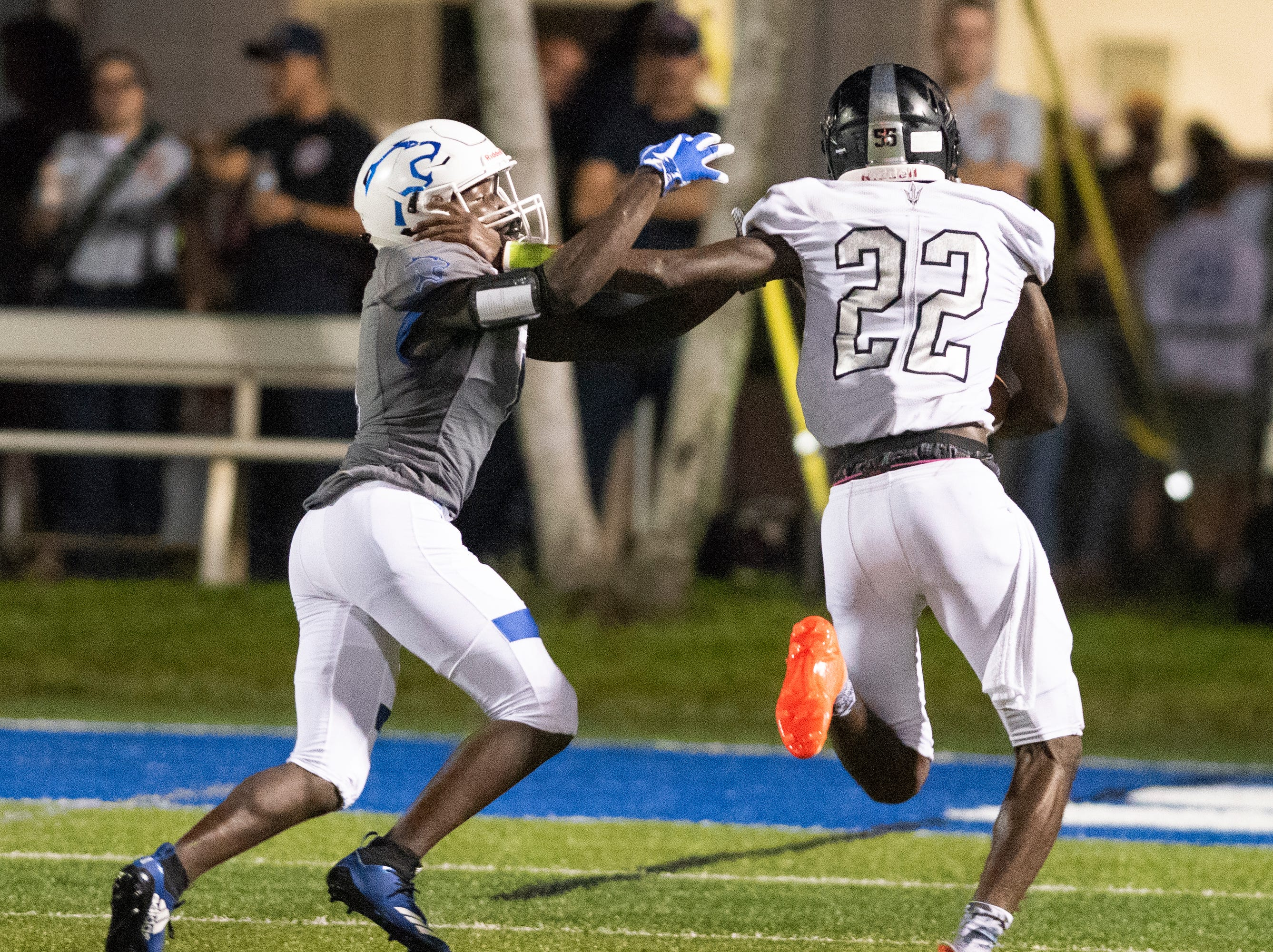 Mariner quarterback Rashawn Hunter stiff arms Deshaun Duverge of Barron Collier on his way to score a touchdown  during the game at Barron Collier High Friday night, September 21, 2018.