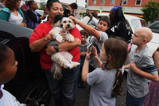 Kookie Morrison throws a birthday party for Innocent, her Yorkie-Bishon Mix dog at Splish Splash Dog Daycare in Englewood on Friday September 21, 2018. Kids gather around as Innocent (being carried by Valerie Johnson) arrives at the party.