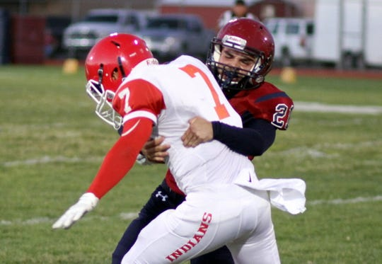 Senior corner Gabriel Reza puts the wraps on on Cobre quarterback Israel Jaurequi during Friday's 42-0 Wildcat win over the Grant County Tribe.