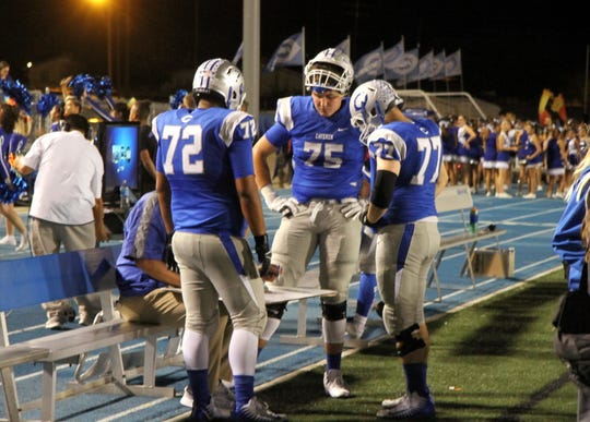 Carlsbad offensive linemen Darius Chavarria (72), Taylor Miterko (75) and Jake Burke (77) look over a diagram during the 2018 Bradley Bowl. All three men were named to the 3-6A All-District Team.