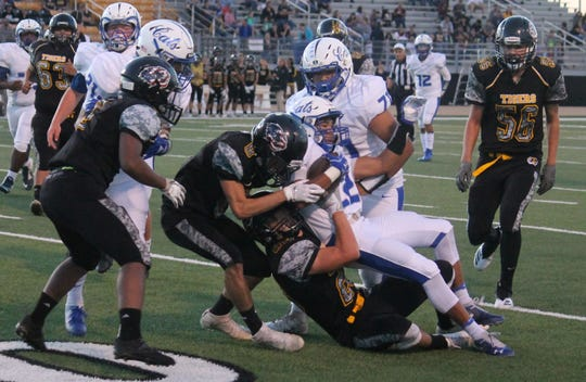Lovington's Sebastian Newman is taken down by a phalanx of Alamogordo Tigers early on in the game on Sept. 21.