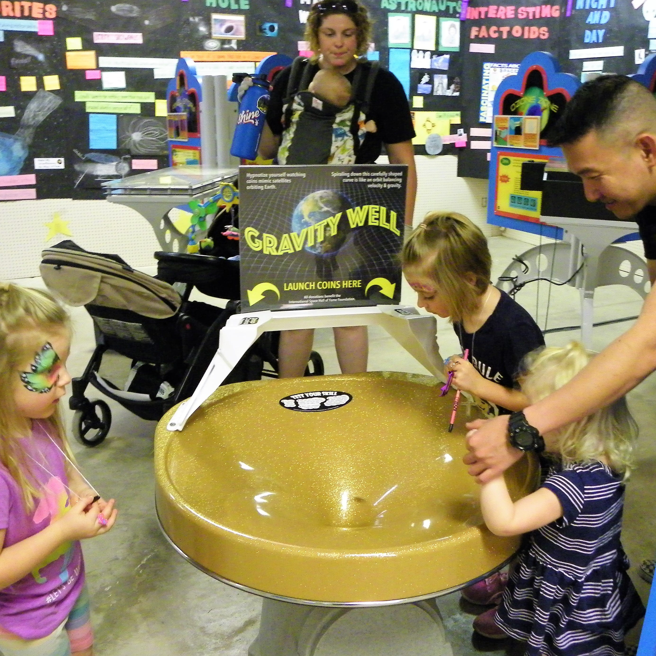 The Watts family watch as a quarter goes around in the Gravity Well at the Otero County Fair.