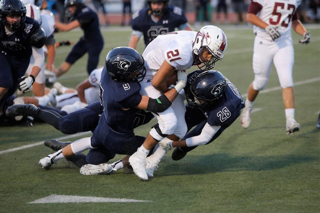 Belen's Anthony Roybal drags Piedra Vista defenders Aiden Ackerman (9) and Tyler Wulfert (28) with him before picking up a first down during Friday's game at Hutchison Stadium.
