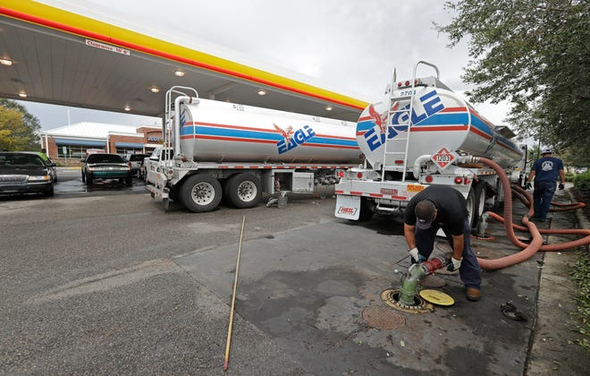 In this Sept. 17, 2018, file photo people wait in line as Travis Hall, right, and Brandon Deese, back, pump fuel from two tanker trucks at a convenience store in Wilmington, N.C.