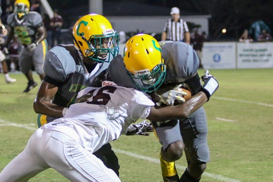 Pensacola Catholic wide receiver Damarius McGhee (6) gets tackled by Pensacola's Mahani Richardson (16) at Catholic High School on Friday, September 21, 2018.