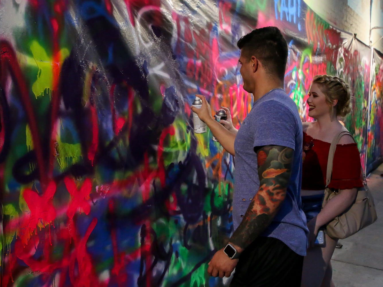 People spray paint Zarzaur Law's Legal Graffiti wall during Gallery Night on Friday, Sept. 21, 2018.