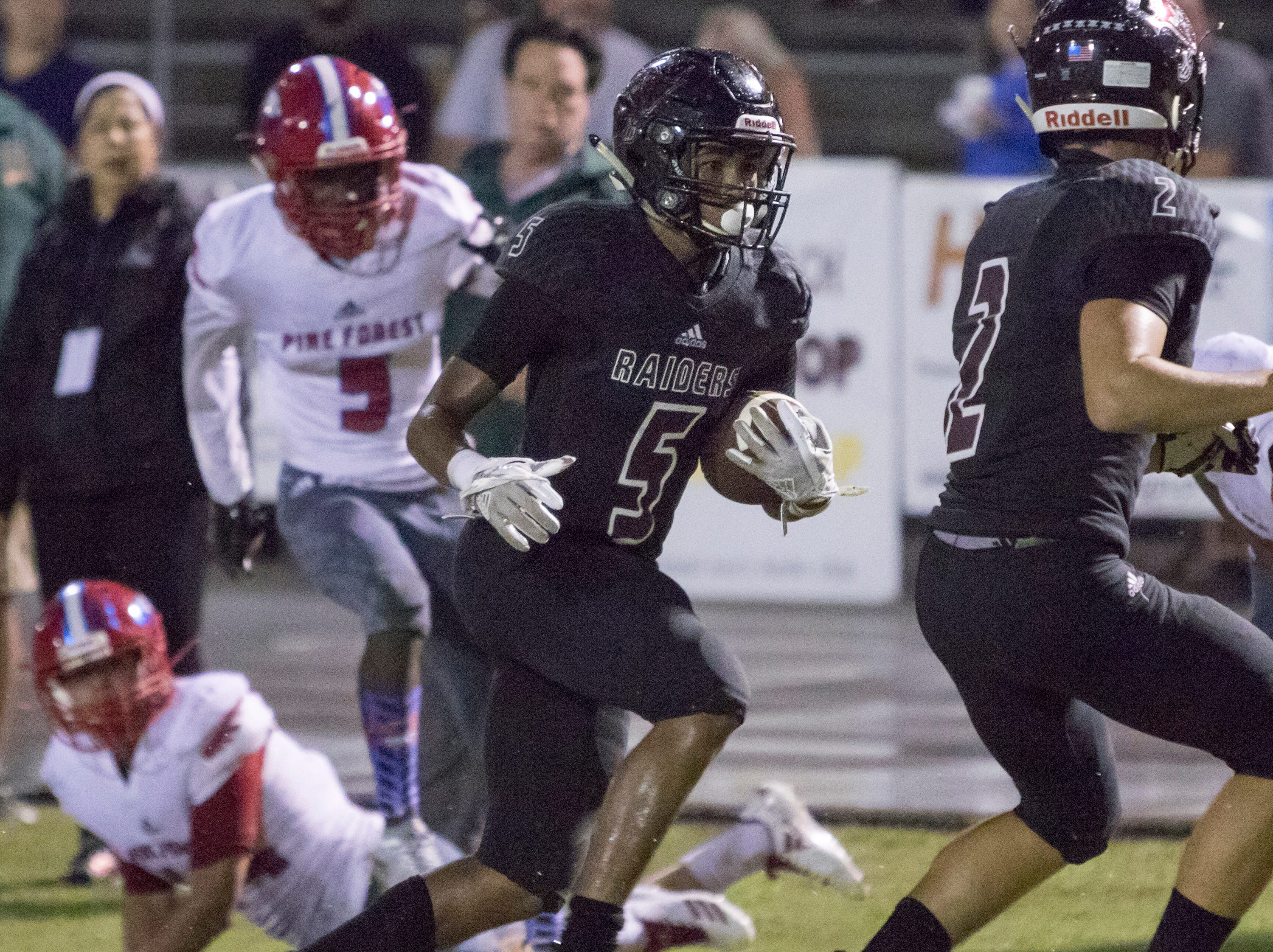 Dante Wright (5) carries for a touchdown and a Raiders 9-6 lead before the added extra point during the Pine Forest vs Navarre football game at Navarre High School in Navarre on Friday, September 21, 2018.