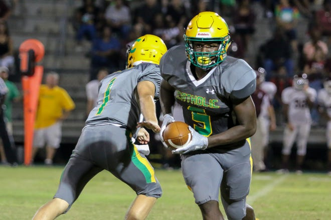 Pensacola Catholic running back Ja'kobi Jackson (5) takes the handoff from quarterback Colin Whibbs (1) and prepares to give the ball to Demarius McGhee during a reverse play against the PHS Tigers at Catholic High School on Friday, September 21, 2018.