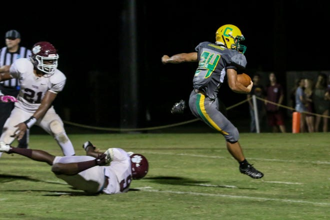 Pensacola Catholic's Seth Wilson (24) jumps over PHS' Ronald Clark (9) and heads to the end zone for a touchdown at Catholic High School on Friday, September 21, 2018.