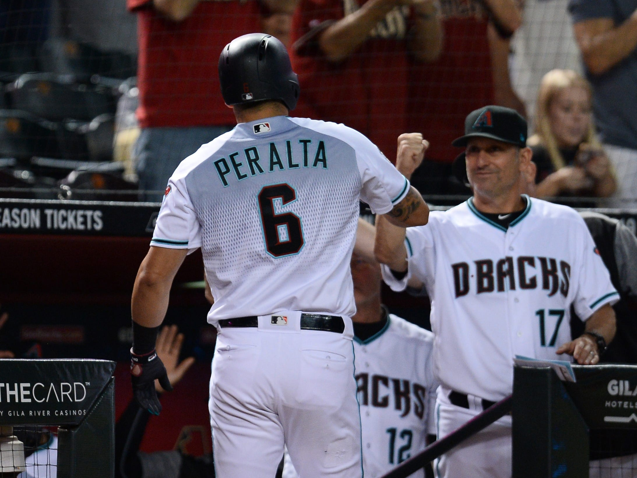 Sep 21, 2018; Phoenix, AZ, USA; Arizona Diamondbacks right fielder David Peralta (6) bumps fists with Arizona Diamondbacks manager Torey Lovullo (17) after hitting a solo home run against the Colorado Rockies during the first inning at Chase Field.