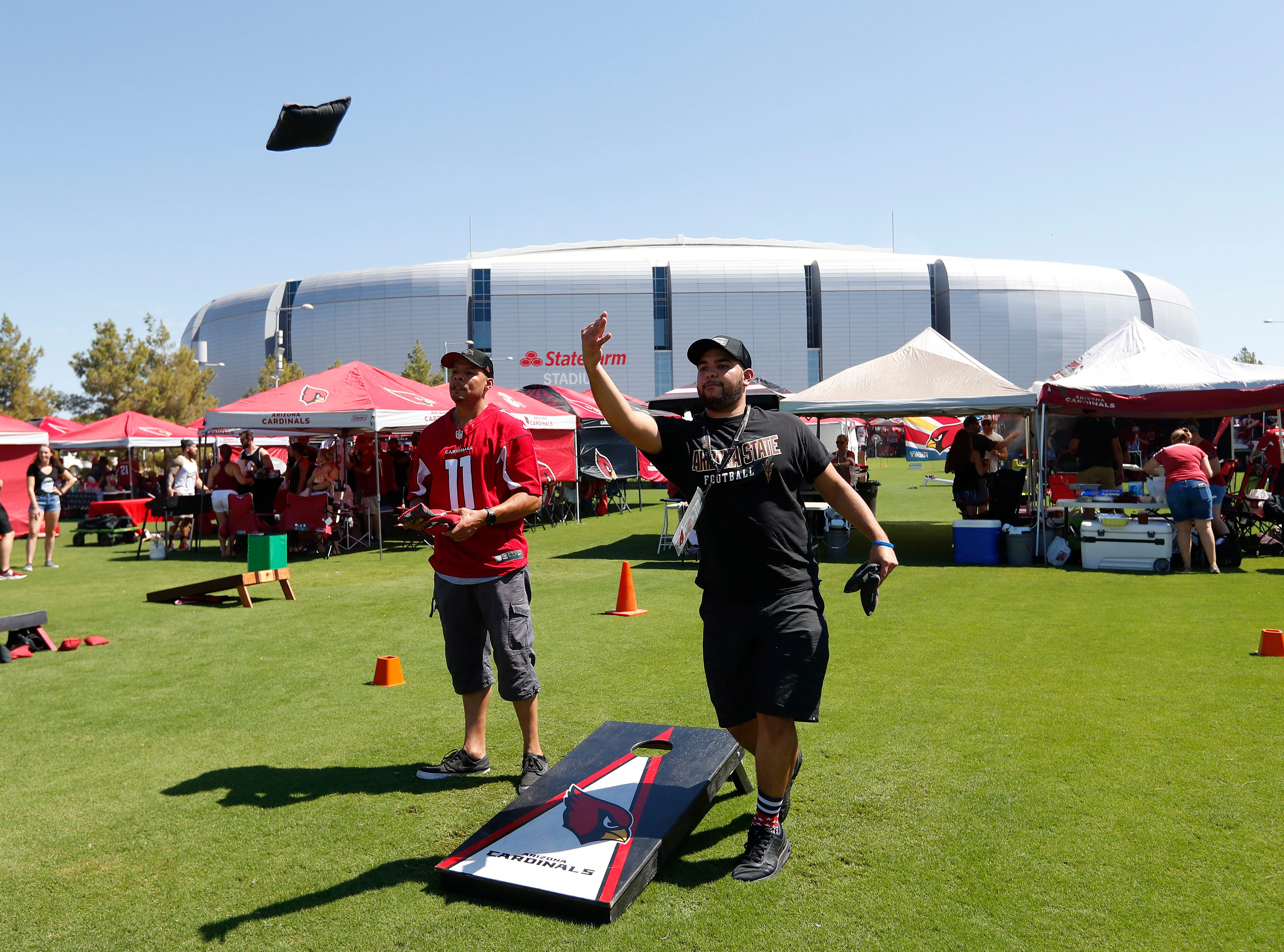 Arizona Cardinals fans Edgar Balenzuela and Michael Clayton, right, toss beanbags priot to an NFL football game against the Washington Redskins, Sunday, Sept. 9, 2018, in Glendale, Ariz.