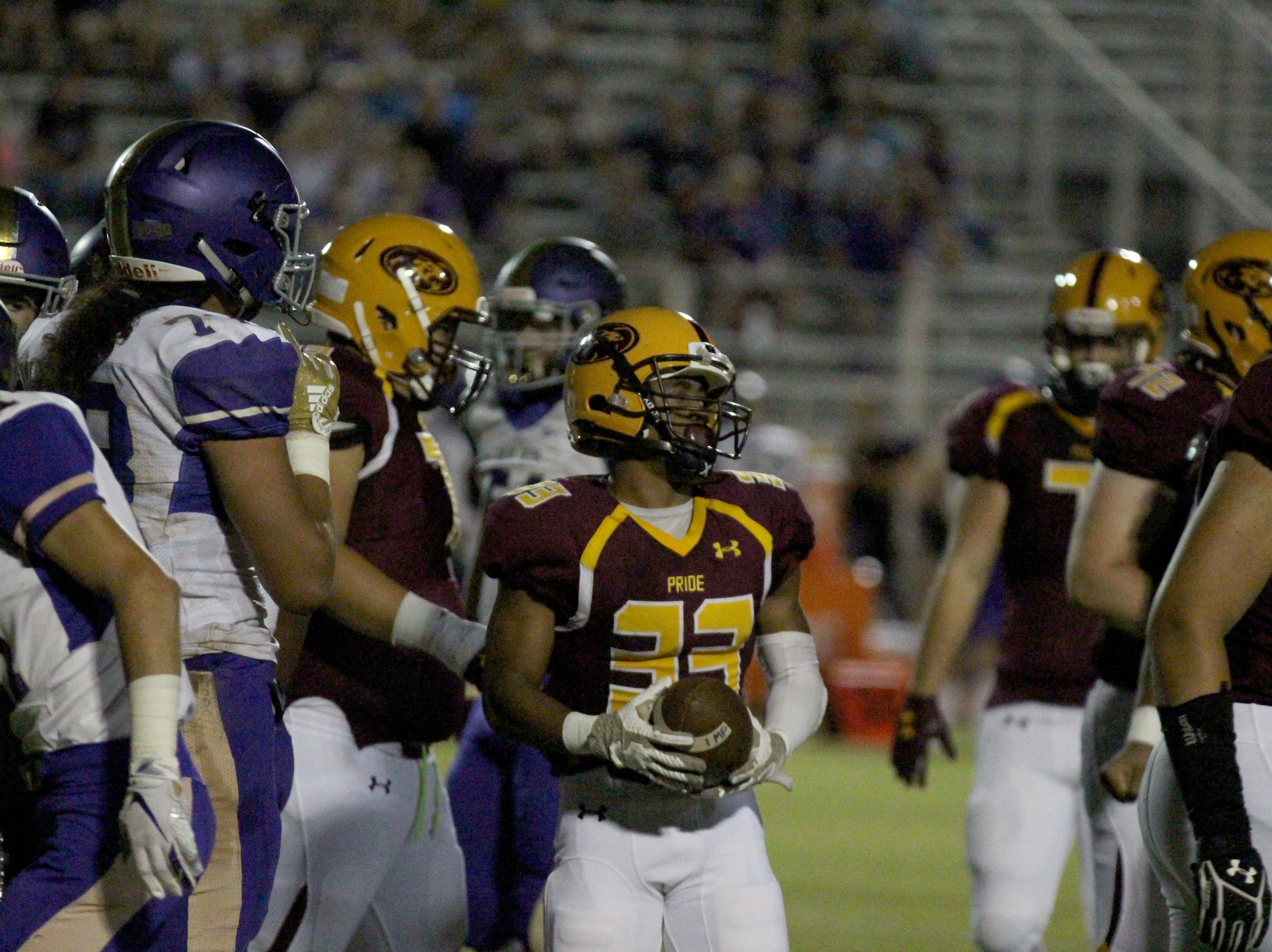 Mountain Pointe's Jakim McKinney holds the ball inbetween a play against Queen Creek on Friday night at Mountain Pointe High School on Sept. 21, 2018.