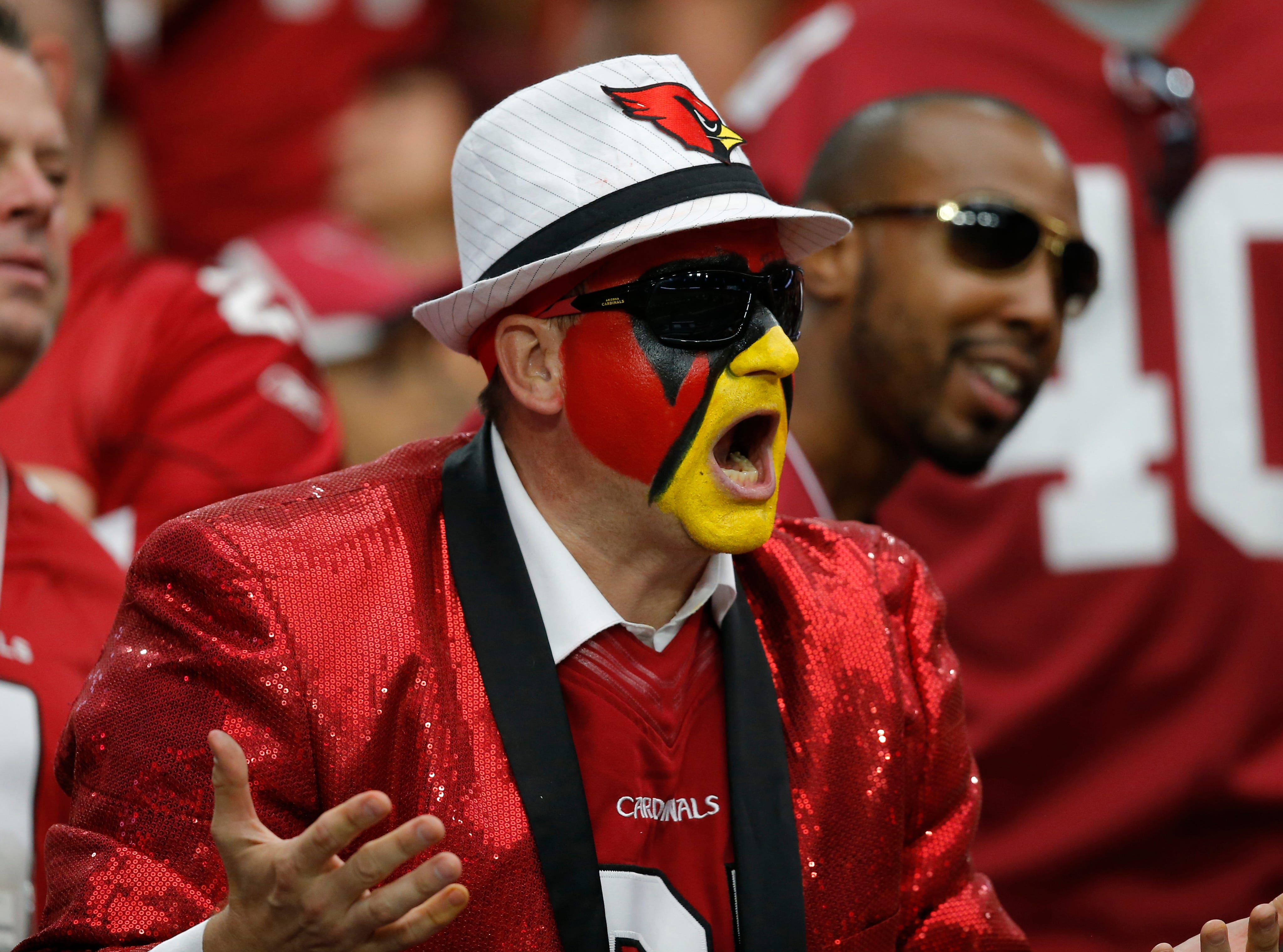An Arizona Cardinals fan cheers during the first half of an NFL football game against the Washington Redskins, Sunday, Sept. 9, 2018, in Glendale, Ariz.