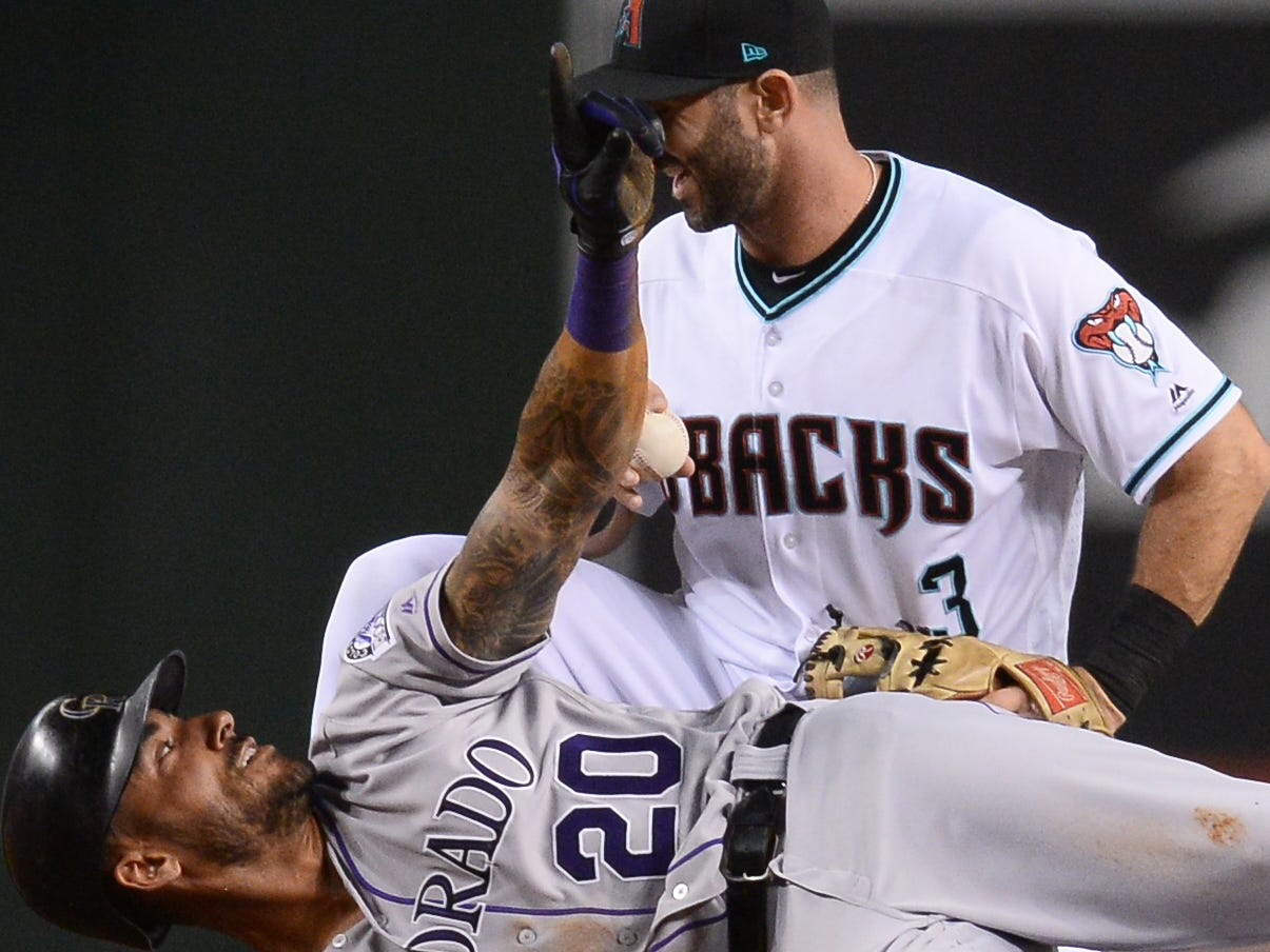 Sep 21, 2018; Phoenix, AZ, USA; Colorado Rockies first baseman Ian Desmond (20) looks up at Arizona Diamondbacks third baseman Daniel Descalso (3) after being tagged out at second base during the fifth inning at Chase Field.