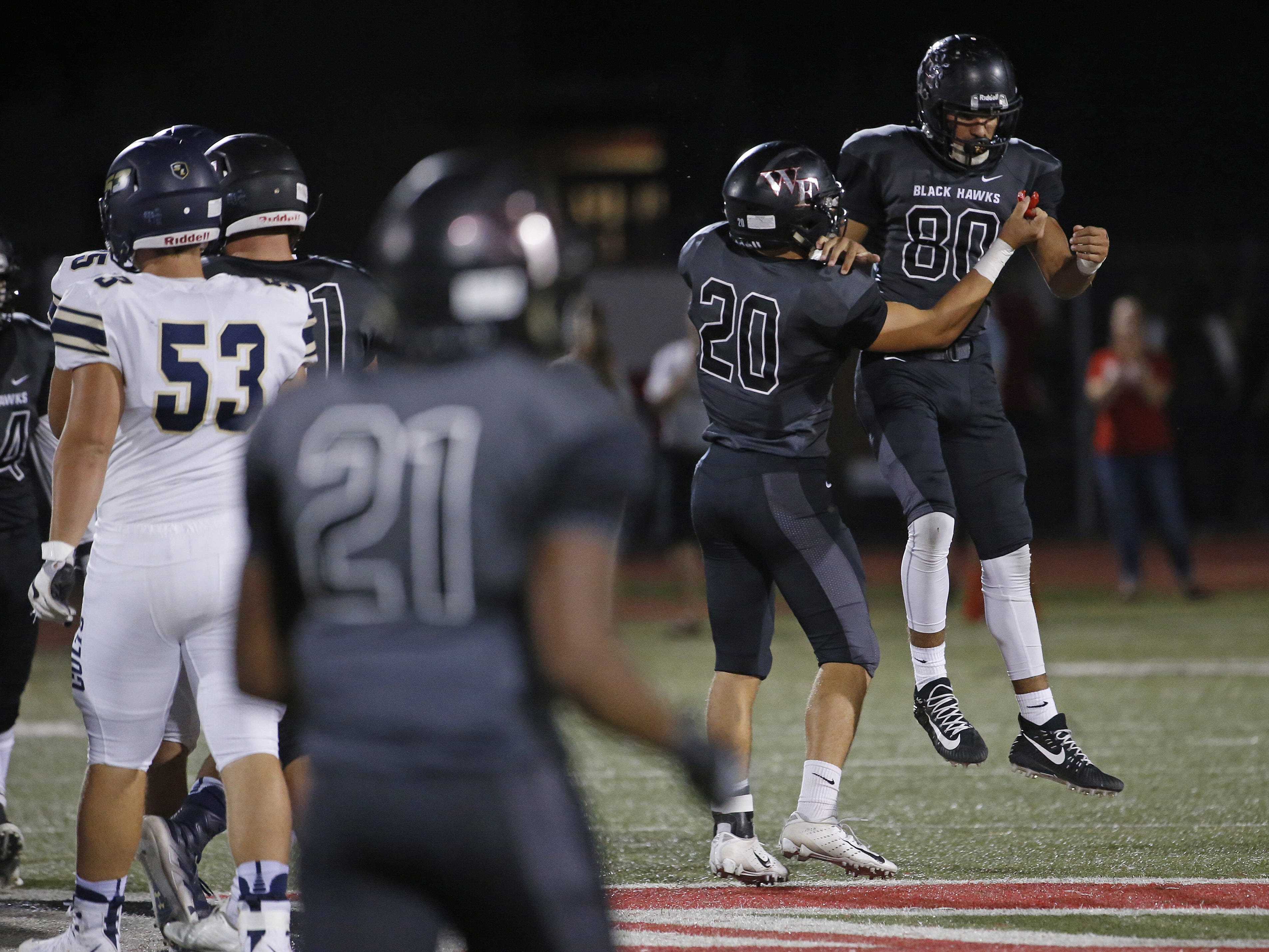 Williams Field's Nick Hernandez (80) and Trey Washburn (20) celebrate a sack against Casteel at Williams Field High School in Gilbert, Ariz. on Sept. 21, 2018.  #azhsfb