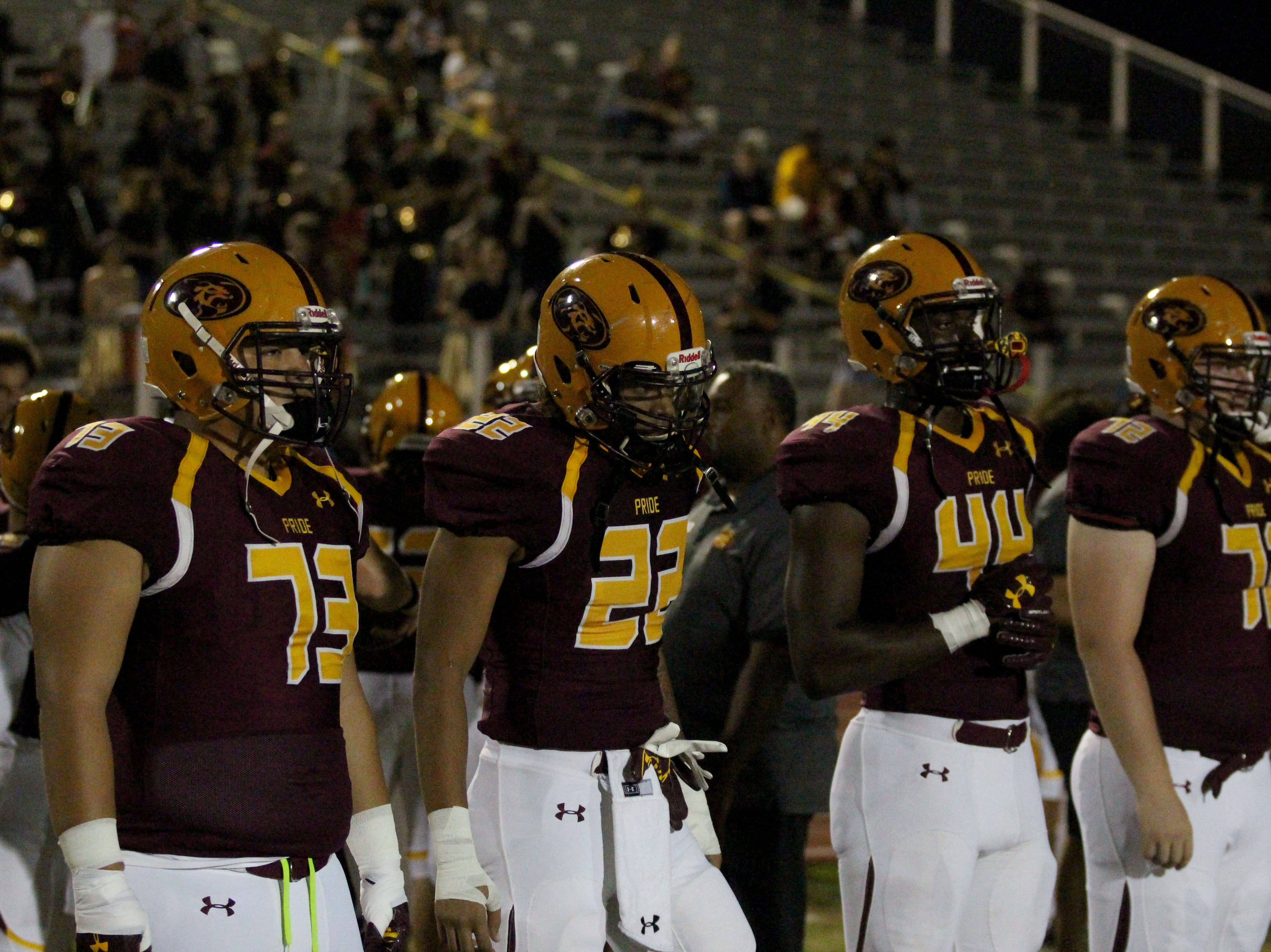 Mountain Pointe captains walk to the middle of the field before the team's game against Queen Creek on Friday night at Mountain Pointe High School on Sept. 21, 2018.
