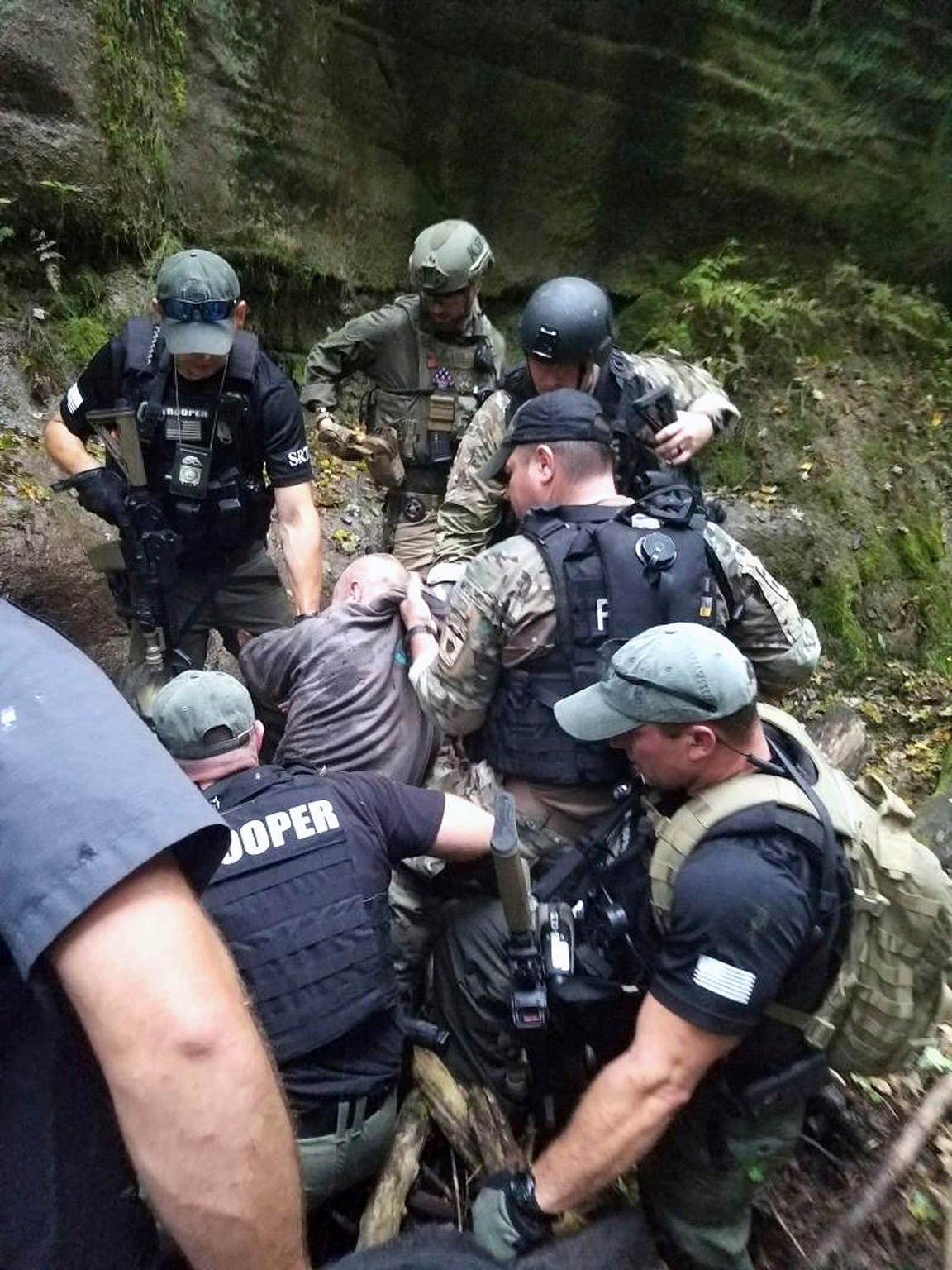 In this photo released by the Ohio State Highway Patrol, Shawn Christy is apprehended in Mifflin Township, near Columbus, Ohio Friday Sept. 21, 2018. The U.S. Marshals Service says Christy, a Pennsylvania man accused of threatening President Donald Trump and law enforcement officials, has been arrested in Ohio. They say Shawn Richard Christy was arrested at 4:45 p.m. Friday in Mifflin Township, near Columbus, by marshals and task force members from Ohio and Pennsylvania. (Ohio State Highway Patrol via AP)