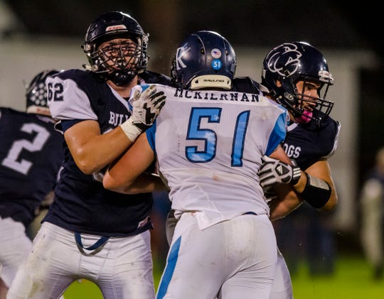 Yale High School tight end Travis Miracle (62) and offensive lineman Steven Klei pushes against Richmond High School's Dan McKiernan  Friday, Sept. 21, 2018, during their game at Yale High School.