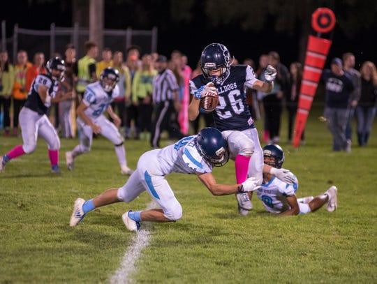 Richmond High School's Matt Barolomucci (14) tackles Yale High School running back Jacob Jonseck Friday, Sept. 21, 2018 during their game at Yale High School.