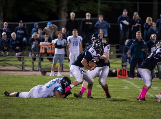 Yale High School quarterback Jacob Craig (2) tries to run the ball after being grabbed by Richmond High School defensive end Connor Cracchiolo Friday, Sept. 21, 2018, during their game at Yale High School.