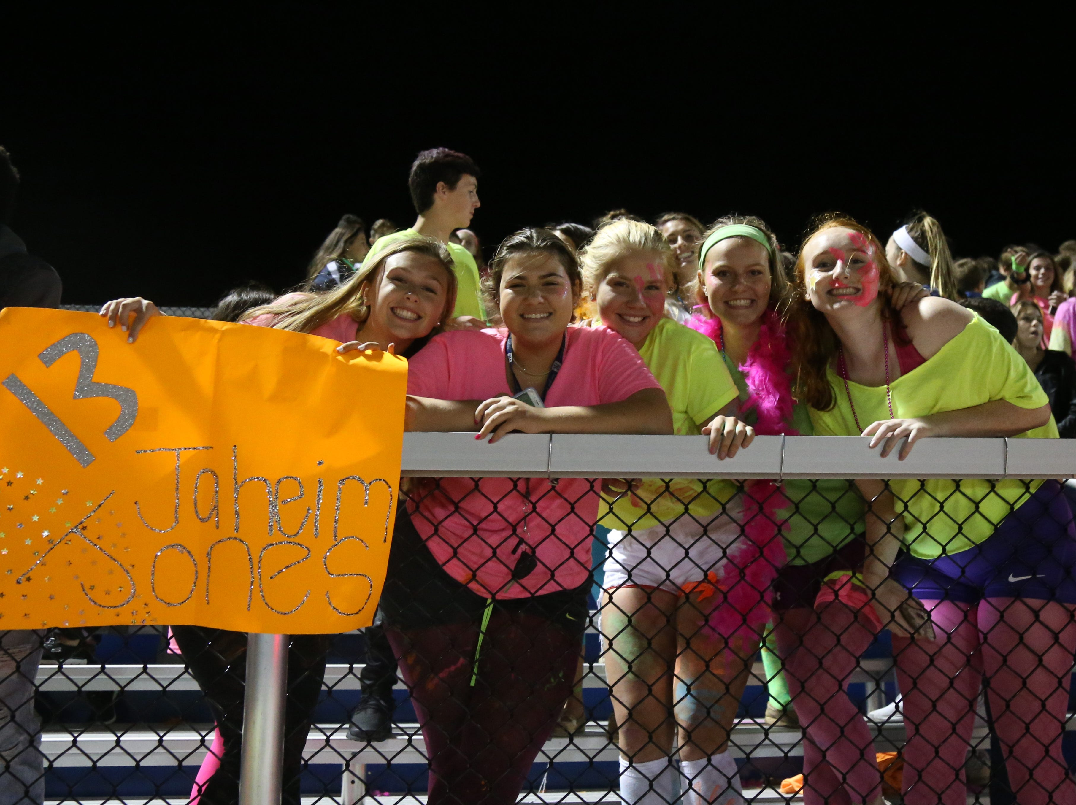 Members of the Our Lady of Lourdes girls soccer team show support for the football team.