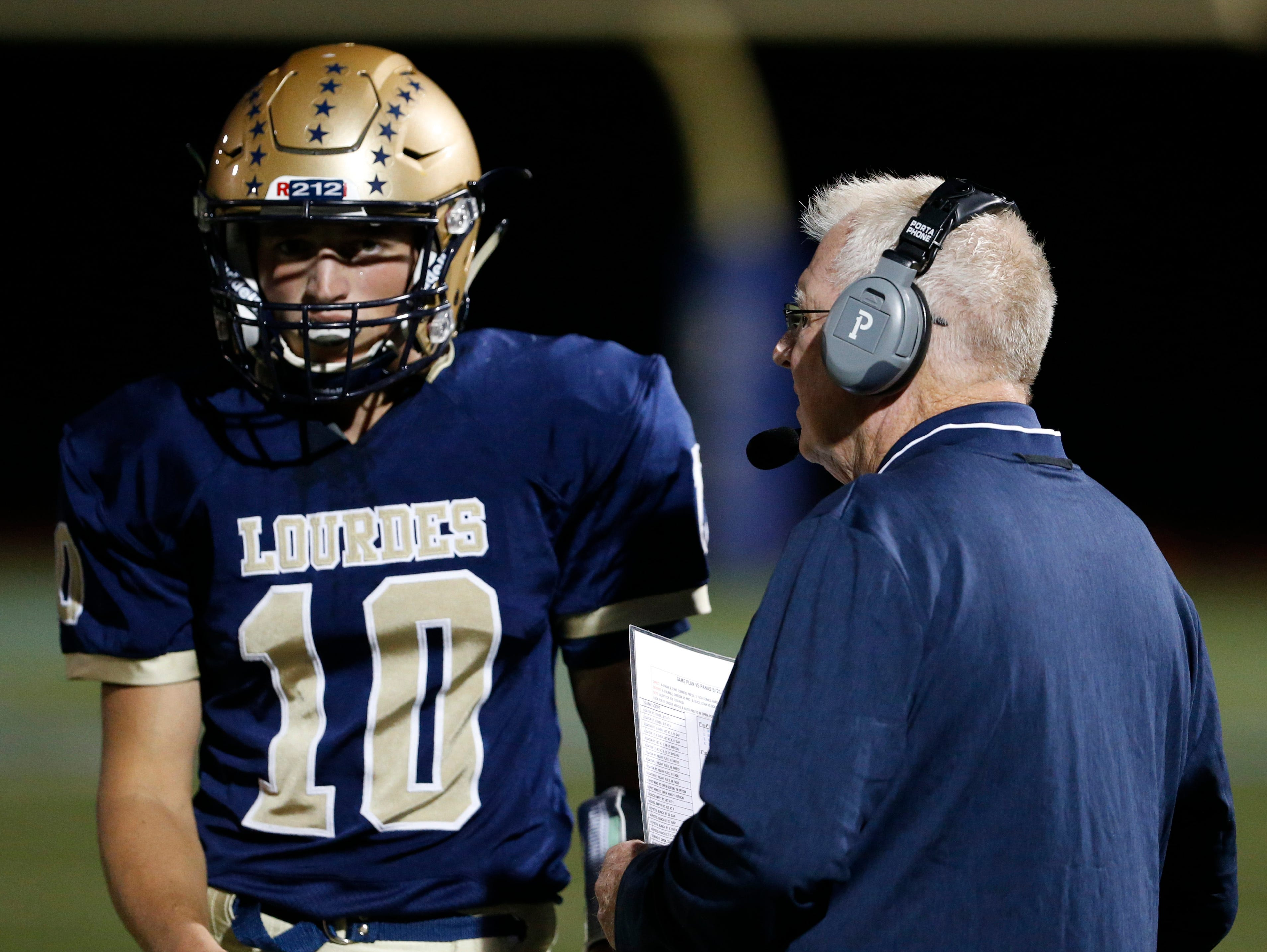 Lourdes quarterback Max Kras gets instructions from head coach Brian Walsh during a Sept. 21 game against Walter Panas.