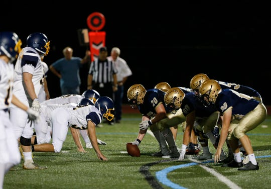 Lourdes center Aiden Laux prepares to snap the ball as Panas' defensive line readies for a play during their September 2018 game. Jake Timm (#52) is lined up at left tackle.