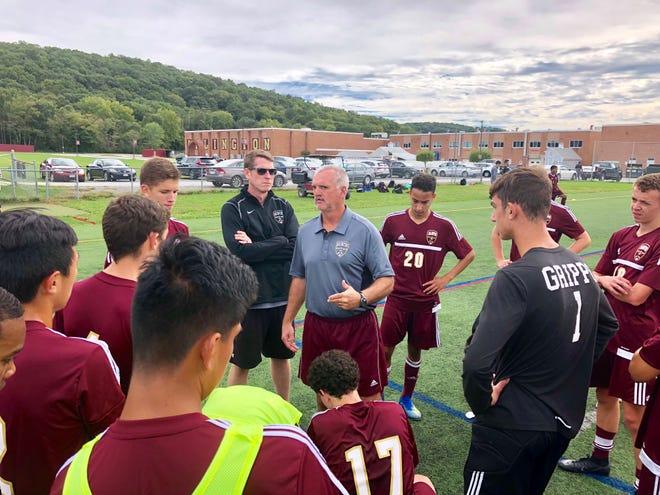 Coach Craig Sanborn huddles his Arlington High School boys soccer team for a post-game talk after its win over Ketcham on Saturday.