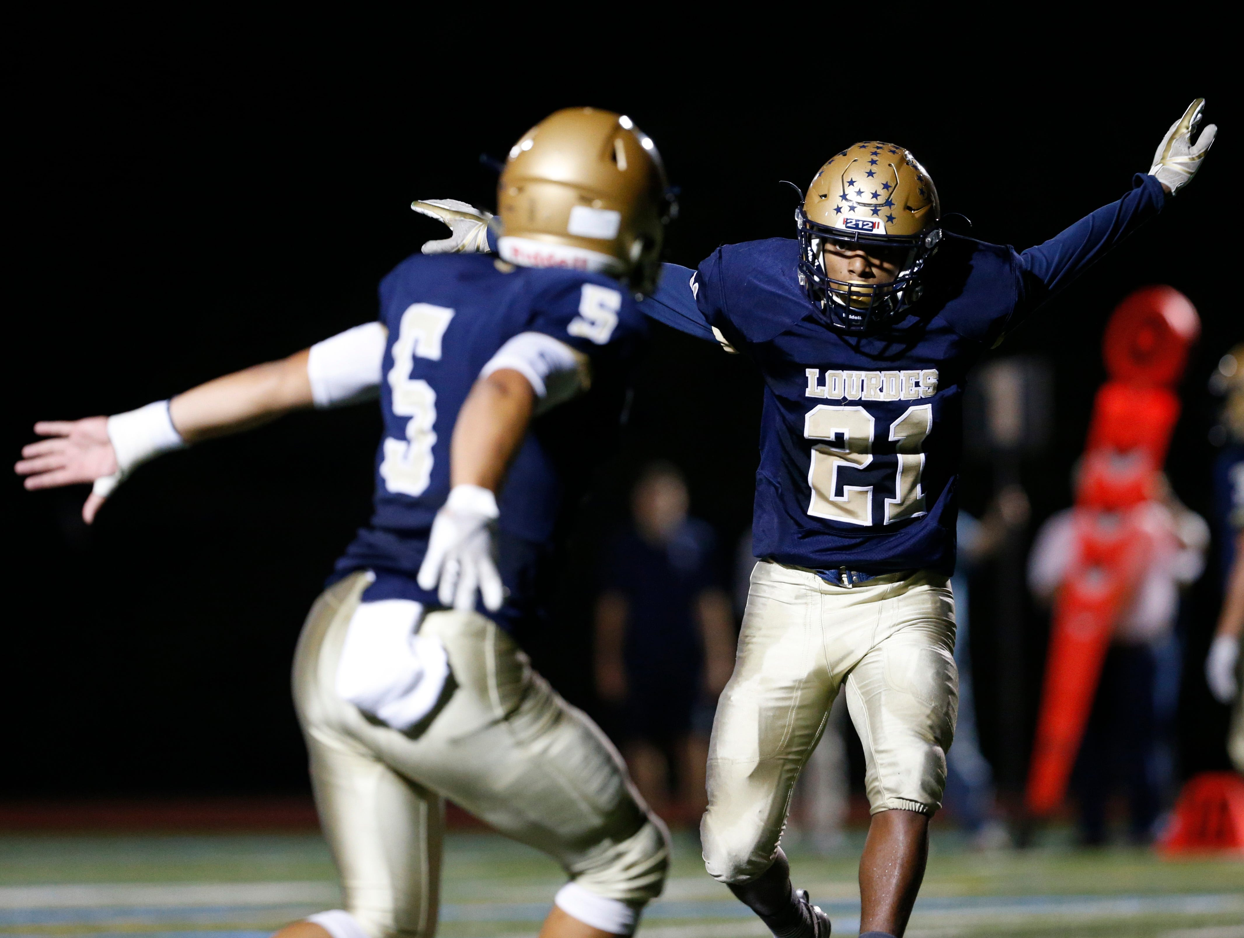 Our Lady of Lourdes football teammates Johnny Wagner (left) and Kyle Strack congratulate each other with a leaping chest bump during their Sept. 21 game against Panas.