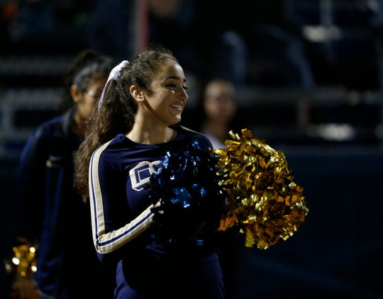 An Our Lady of Lourdes cheerleader looks on smiling during the football team's dominant win over Panas on Friday.