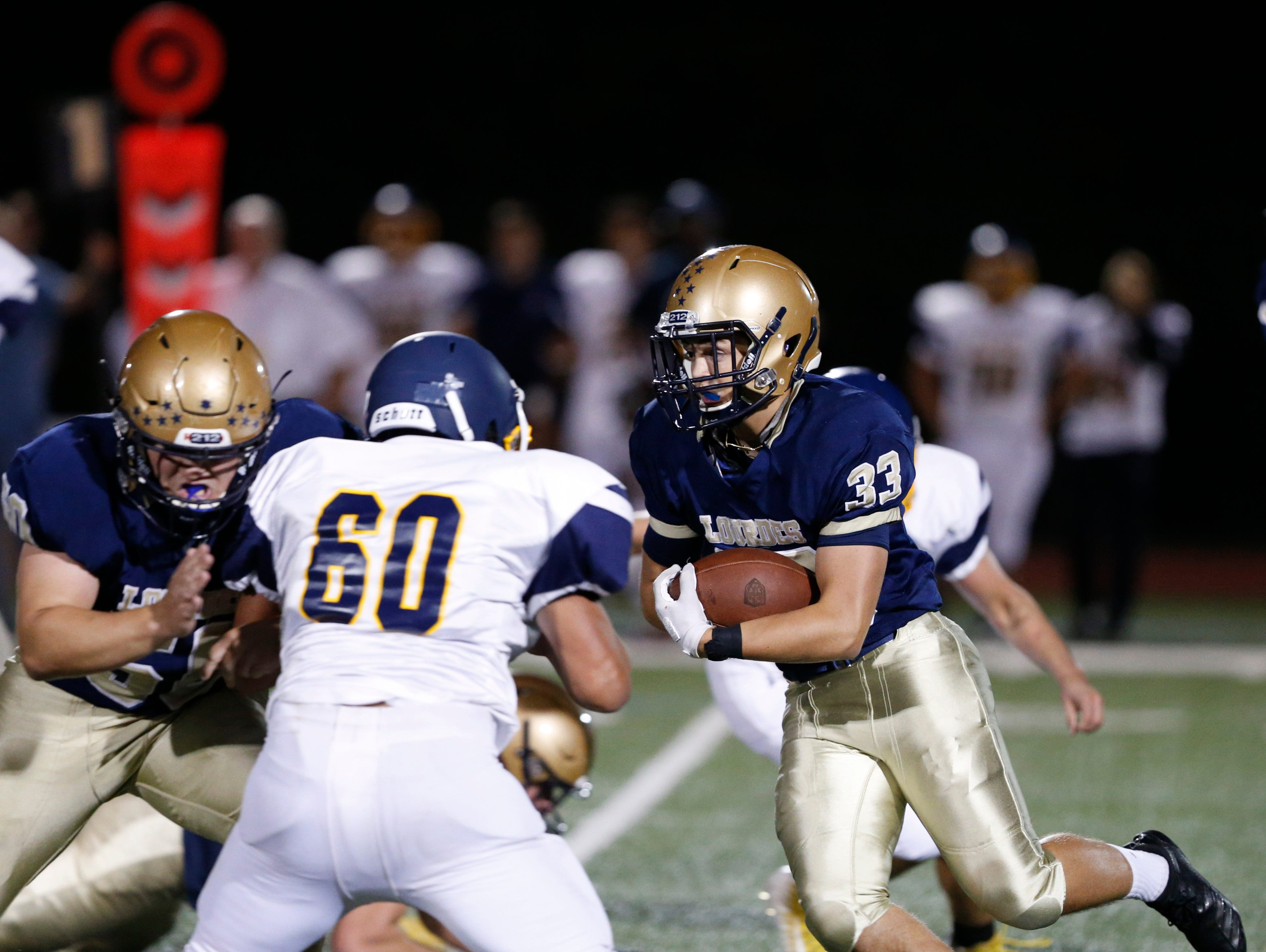 Lourdes' Connor Gioia finds a hole created by Kevin Johansson blocking Panas' William Calderon during Friday night's game at Lourdes on Sept. 21, 2018.
