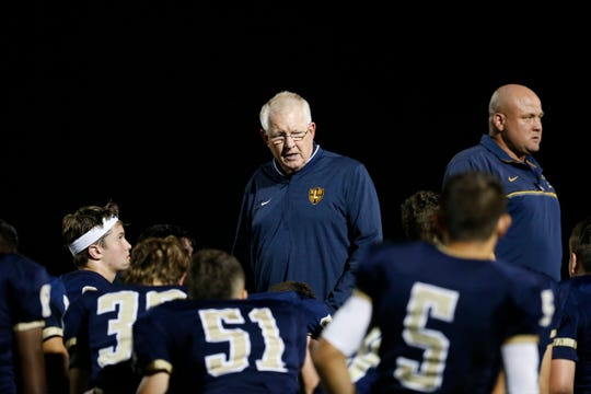 Head coach Brian Walsh addresses his Lourdes football team in a post-game huddle after its big win over Panas on Friday.