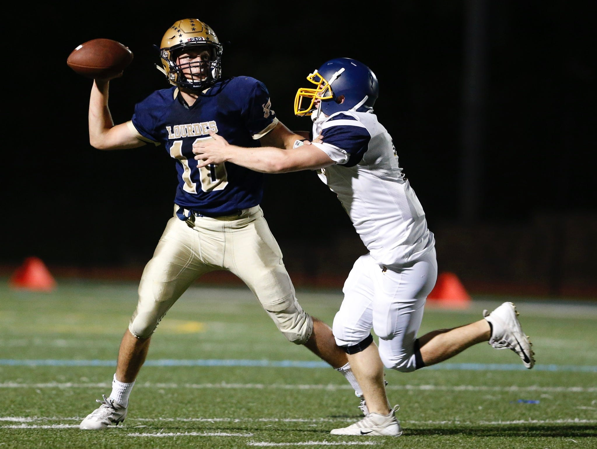 Panas' Jack O'Brien closes in on Lourdes' Max Kras as he passes the ball to Kyle Strack to score in the second quarter of Friday's game on Sept. 21, 2018.