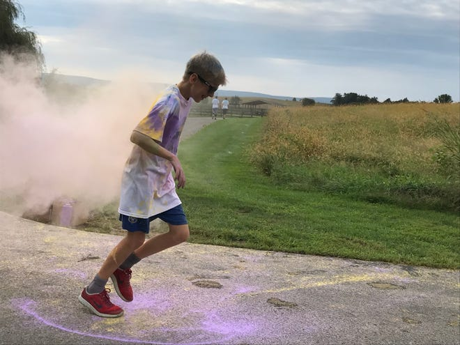 A boy runs out of a cloud of purple and yellow corn starch on Saturday, Sept. 22, 2018, at the ITP Matters Color Run at Norlo Park, Fayetteville.