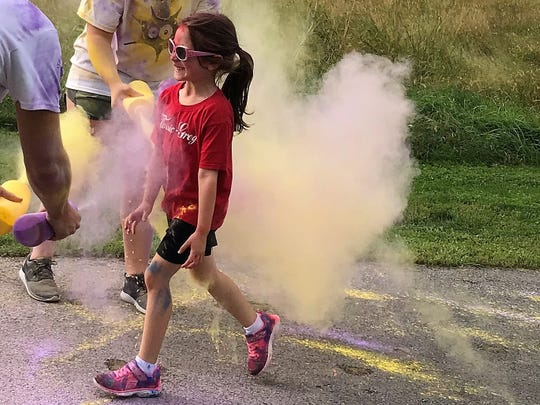 A girl smiles as Jaden Hood of Huntingdon, left, and Christopher Sanbower of Chambersburg, right, douse her in purple and yellow cornstarch on Saturday, Sept. 22, 2018, at the ITP Matters Color Run at Norlo Park, Fayetteville.