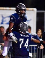 Dallastown center Raymond Christas (74) celebrates a Nyzair Smith touchdown by picking up the running back during the Wildcats' 41-25 win over Northeastern last Friday. Dawn J. Sagert photo.