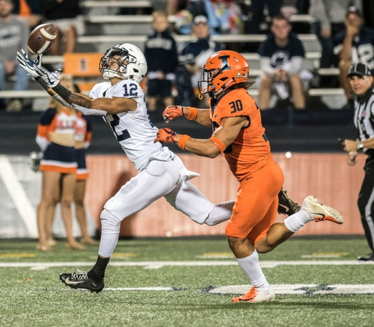Penn State wide receiver Mac Hippenhammer (12) makes a catch as he is pursued by Illinois' Sydney Brown (30) during the second half of an NCAA college football game Friday, Sept. 21, 2018, in Champaign, Ill. (AP Photo/Holly Hart)