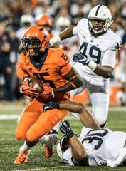 Illinois wide receiver Trenard Davis (15) is tackled by Penn State's Kevin Givens (30) during the second half of an NCAA college football game Friday, Sept. 21, 2018, in Champaign, Ill. (AP Photo/Holly Hart)