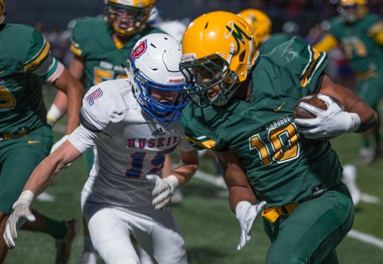 Manogue's Peyton Dixon 10) is hit by Reno's Taskar Eason(15) in their football game played on Friday night